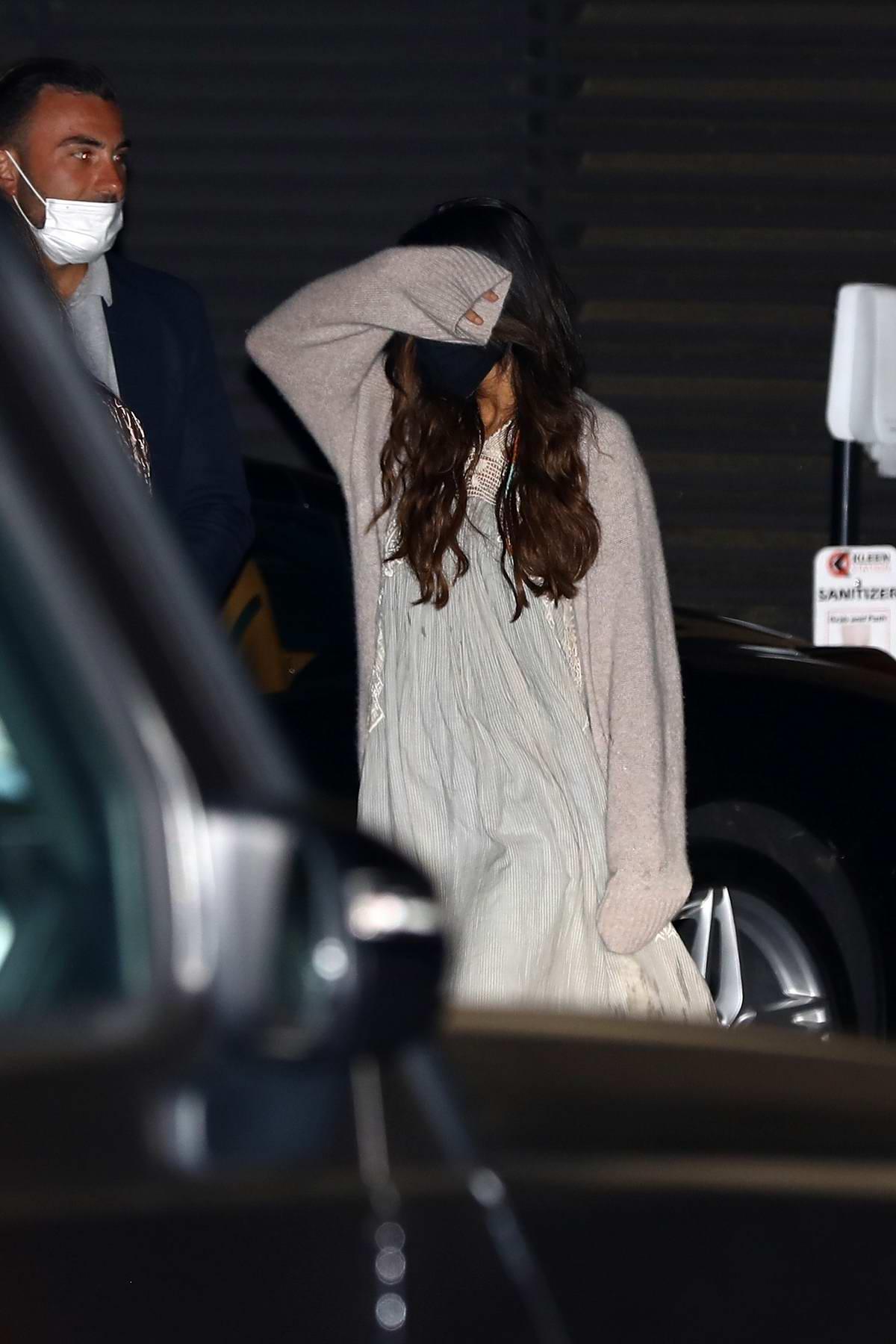Selena Gomez walks behind a friend avoiding cameras after a dinner party at Nobu in Malibu, California