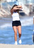 Sofia Richie covers her face in the wind as she walks on the beach with friends in Malibu, California