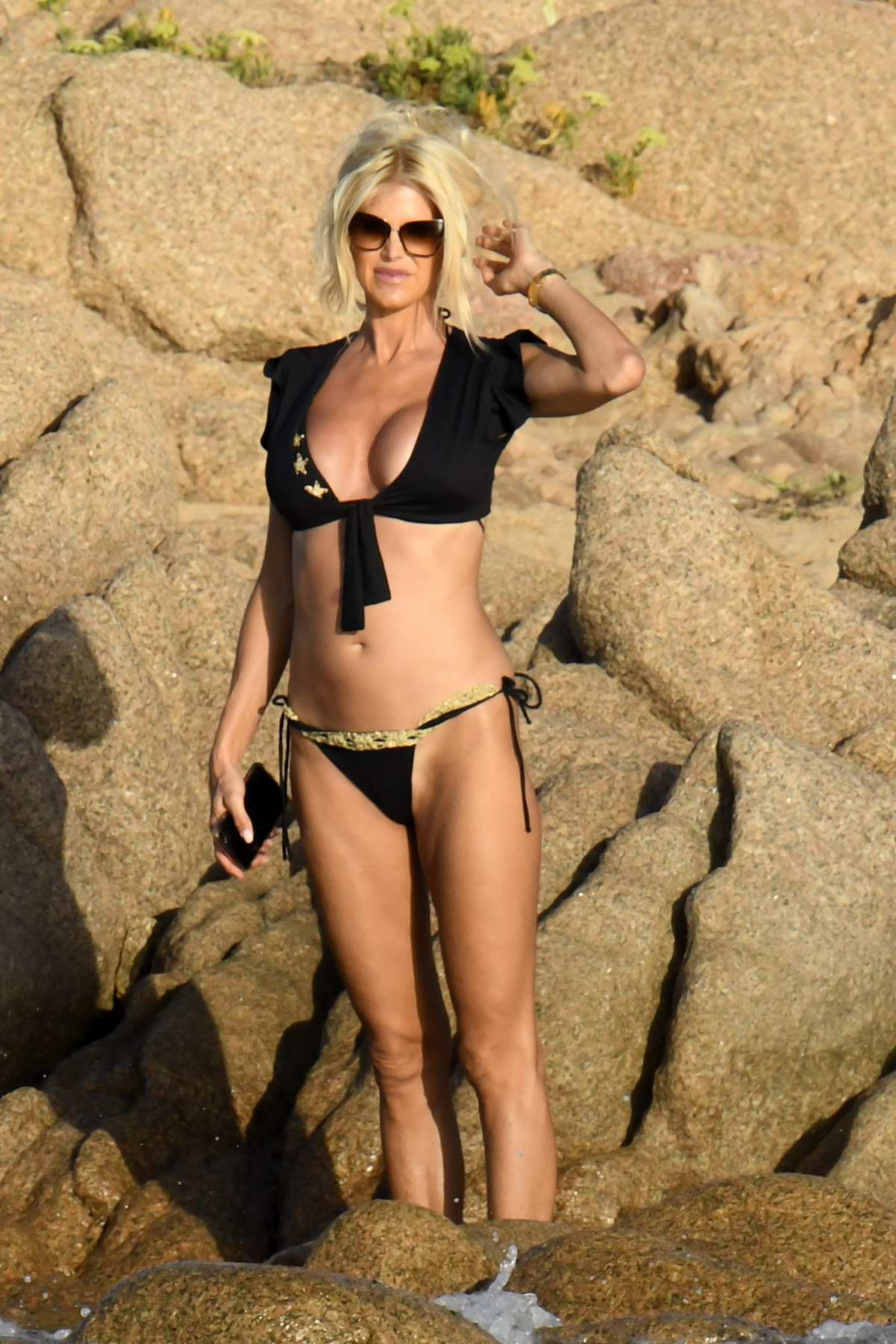 Victoria Silvstedt sizzles in a black bikini while relaxing with boyfriend Maurice Dabbah at her hotel in Porto Cervo, Italy