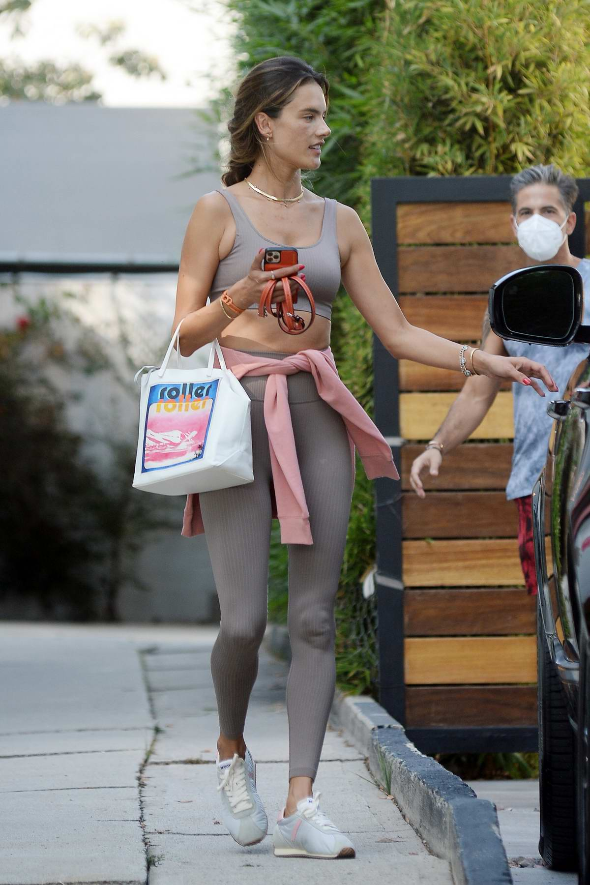 Alessandra Ambrosio shows off her toned figure in a striped workout top and leggings as she leaves a gym in Los Angeles