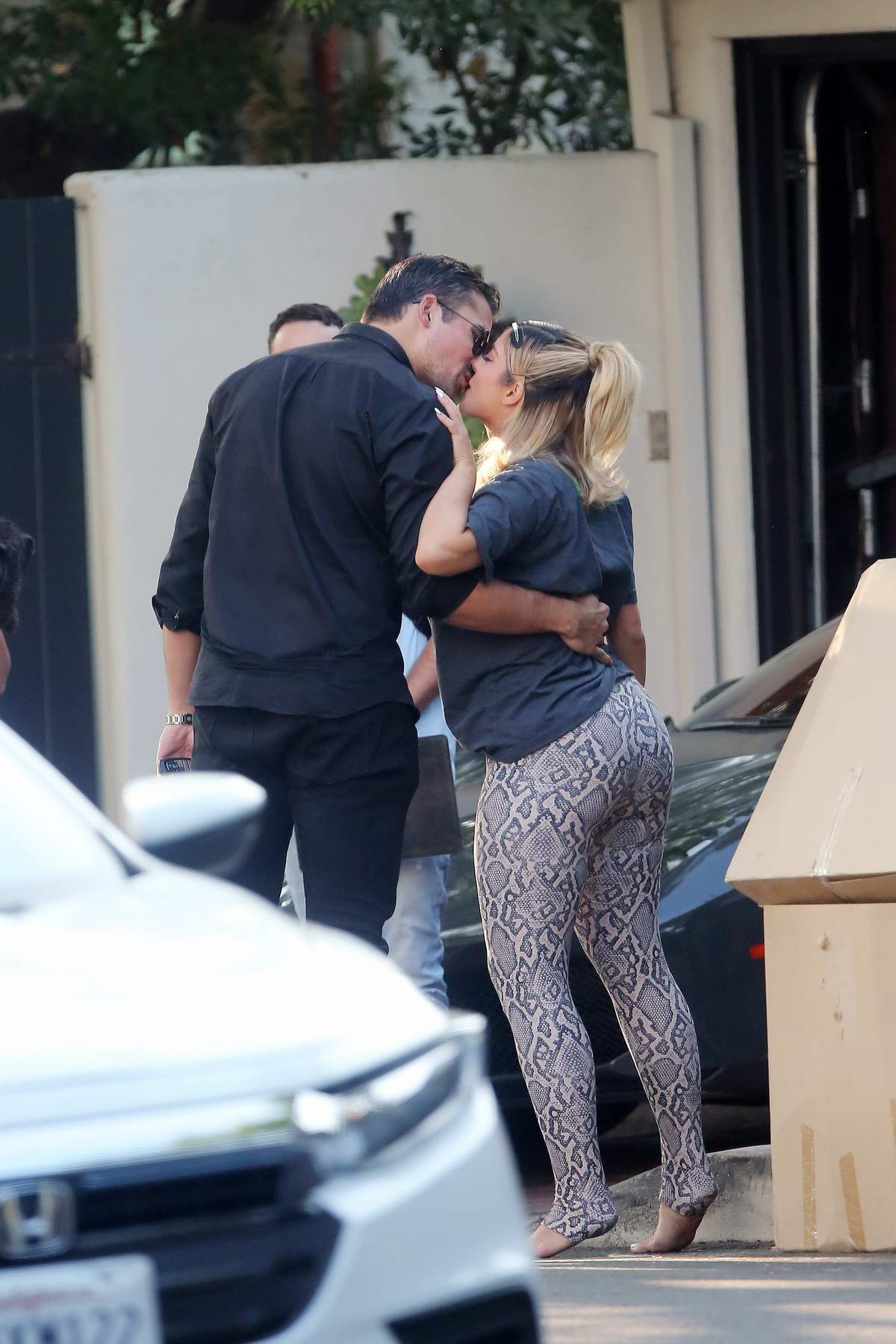 Bebe Rexha shares a kiss with new boyfriend Keyan Safyari as she gets a new Ferrari delivered to her home in Los Angeles