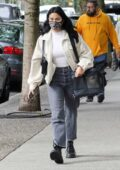 Camila Mendes carries her dog Truffle in a travel bag as she waits for an Uber in Vancouver, Canada