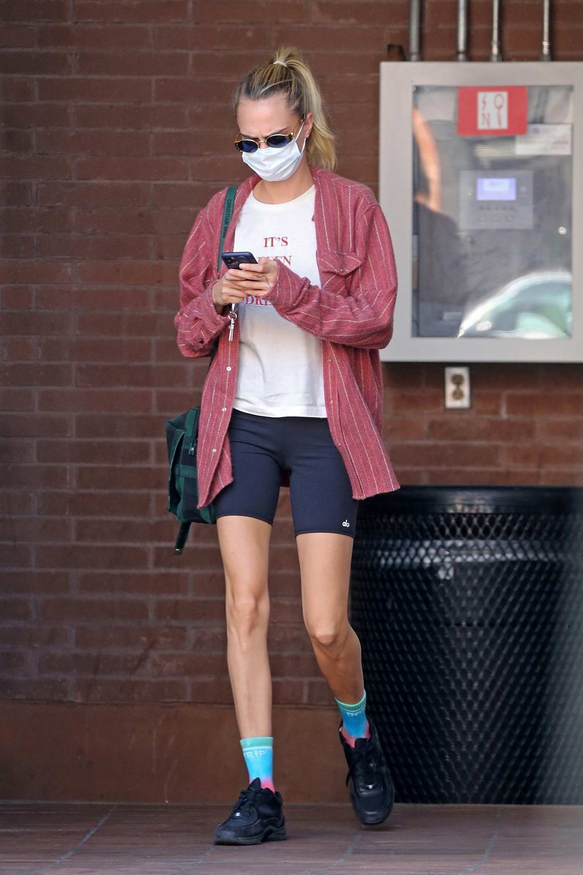 Cara Delevingne wears a red shirt with black bike shorts while heading to a medical building in Beverly Hills, California