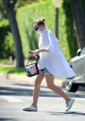 Dakota Fanning wears an oversized white shirt and denim shorts while out driving around in Los Angeles