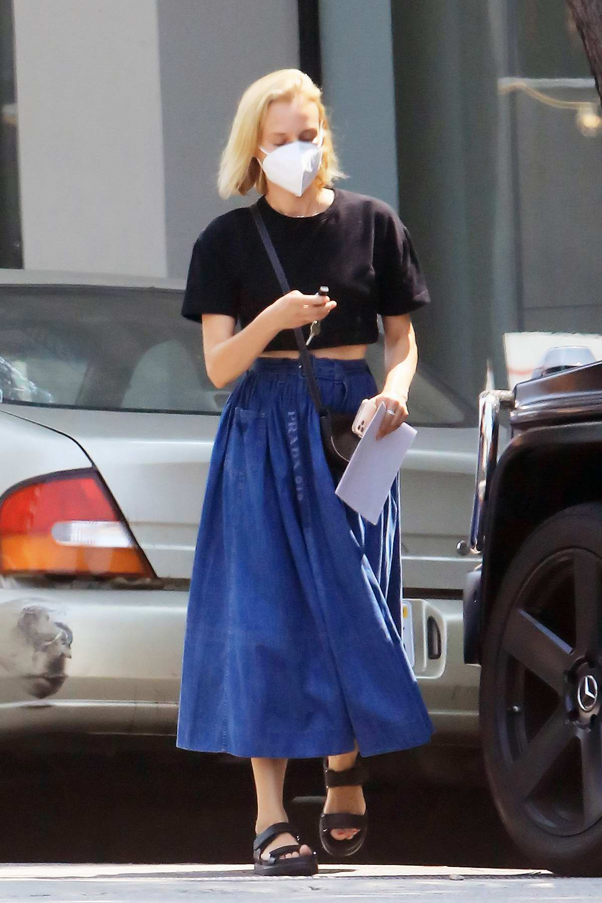 Diane Kruger wears a black crop top and denim skirt while shopping groceries at Bristol Farms in Los Angeles