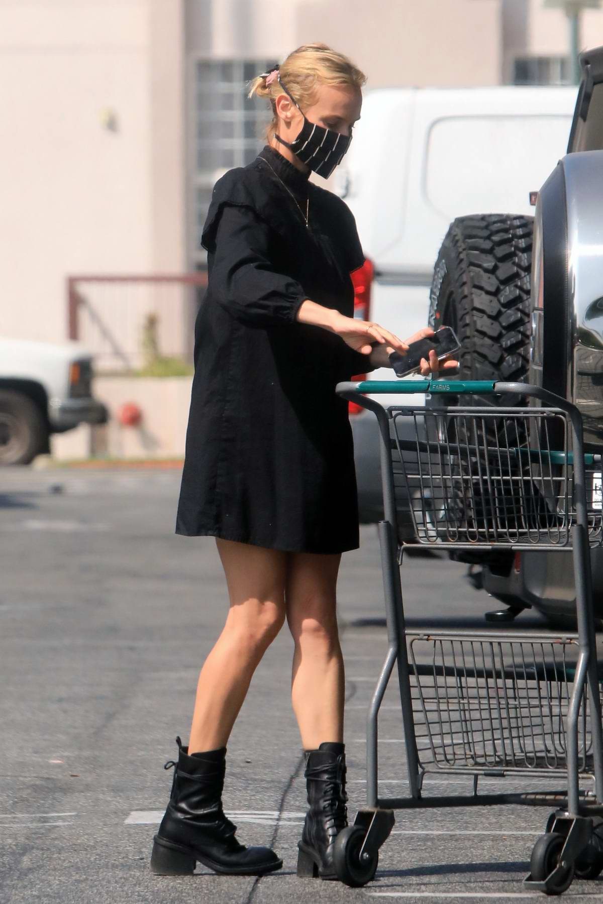 Diane Kruger wears a short black dress and combat boots while shopping groceries at Bristol Farms in Los Angeles