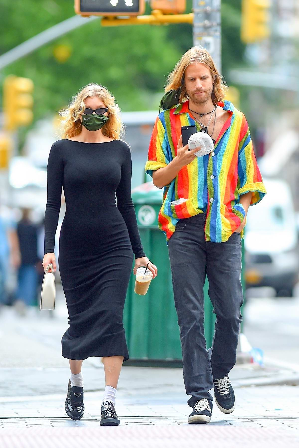 Elsa Hosk shows her baby bump in a form-fitting black dress while out for a coffee run in New York City