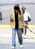 Emily Ratajkowski wears a beige blazer with a black top and ripped jeans while out for stroll with her dog in New York City