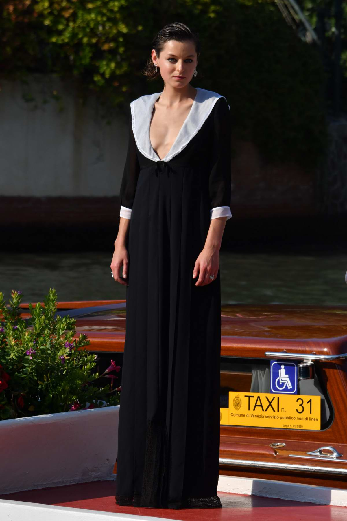 Emma Corrin looks chic in a black dress as she arrives at the 77th Venice Film Festival in Venice, Italy