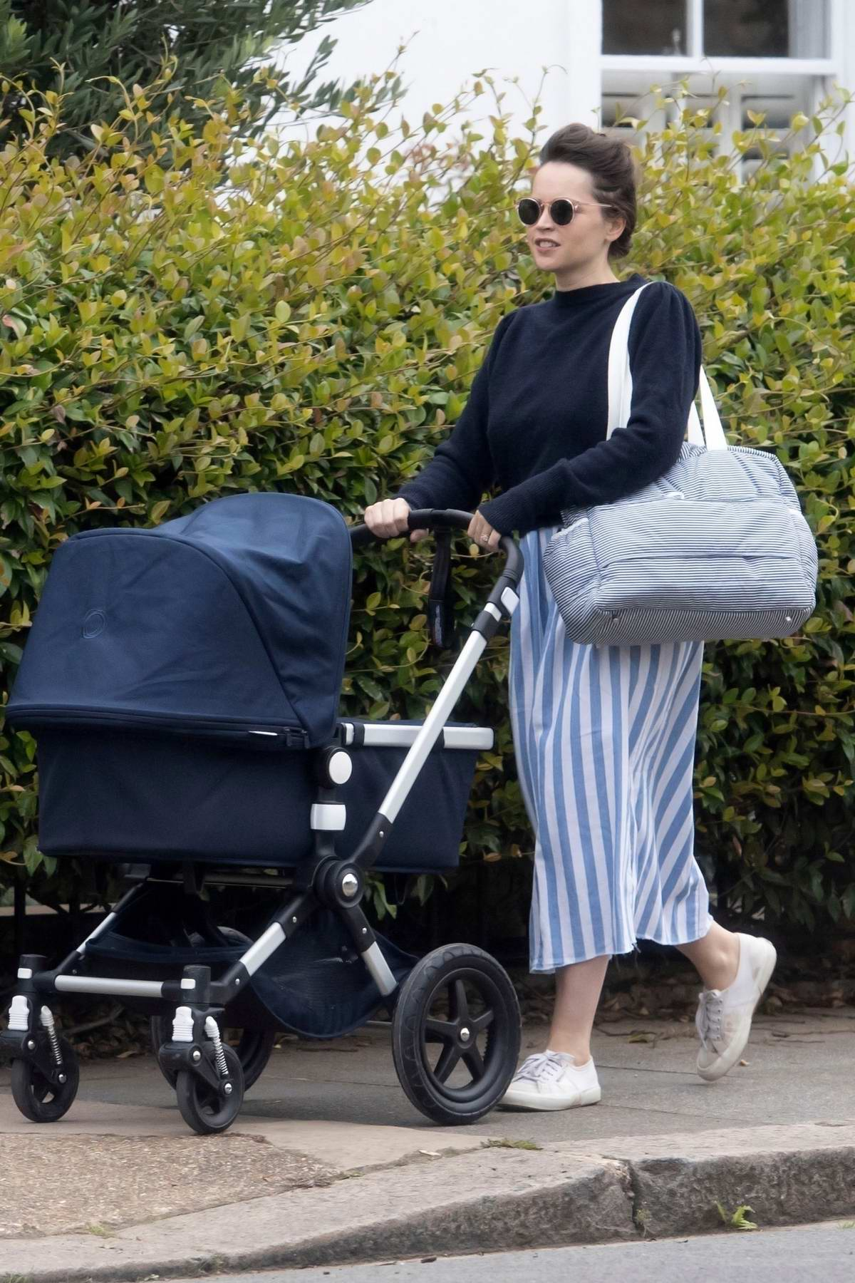 Felicity Jones seen for the first time since giving birth as she takes her newborn for a stroll in London, UK