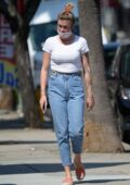 Ireland Baldwin wears a white crop top and jeans while out shopping for vintage clothes in Sherman Oaks, California