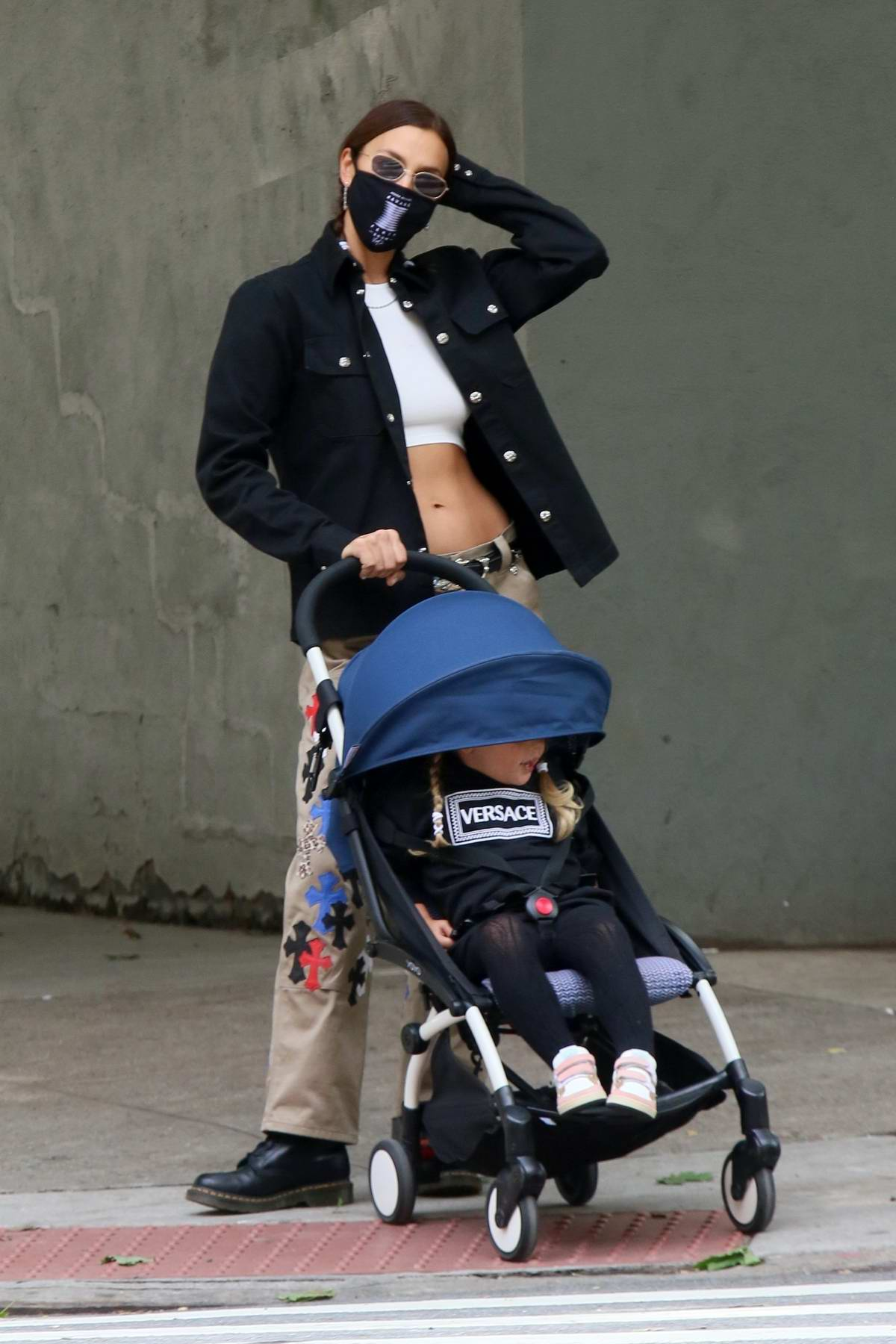 Irina Shayk dons a midriff baring crop top while out for a walk with her daughter around the neighborhood in New York City