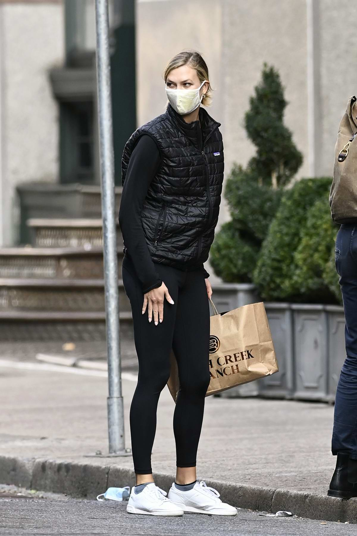 Karlie Kloss sports black sleeveless puffy jacket and leggings as she arrives home with husband Joshua Kushner in New York City