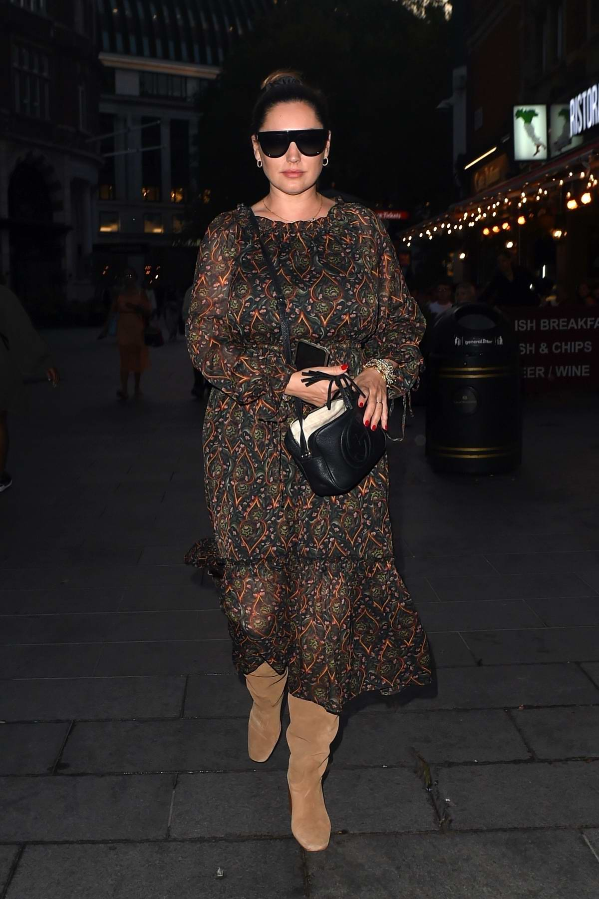 Kelly Brook seen wearing a dark floral print dress with suede boots as she leaves Global Radio in London, UK