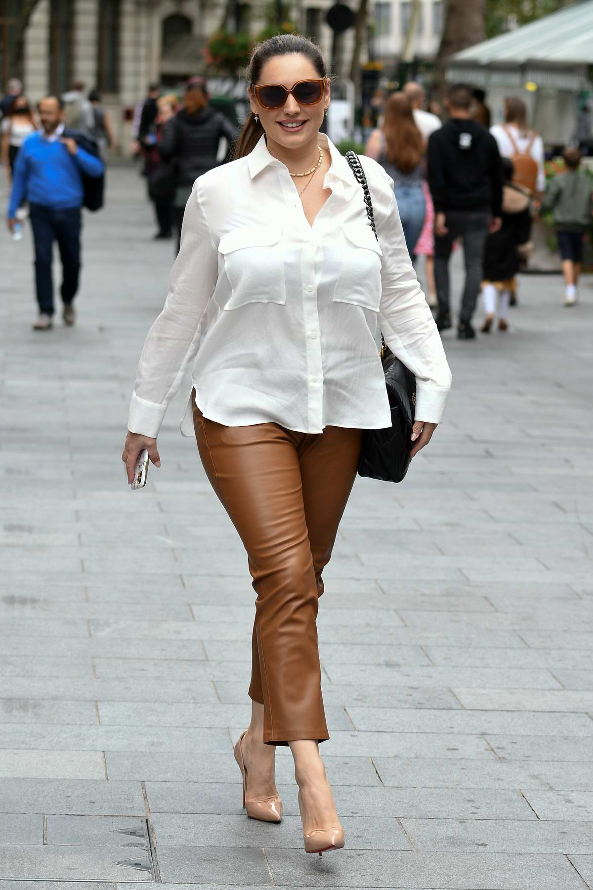 Kelly Brook wears a white shirt and tan leather pants as she arrives at the Global Radio Studios in London, UK