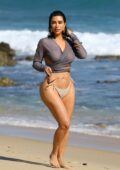 Kim Kardashian looks amazing in a long sleeve crop top and beige bikini bottoms while walking down the beach in Malibu, California