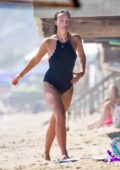 Olivia Wilde looks amazing in a black swimsuit as she cools down in the ocean with a friend in Malibu, California