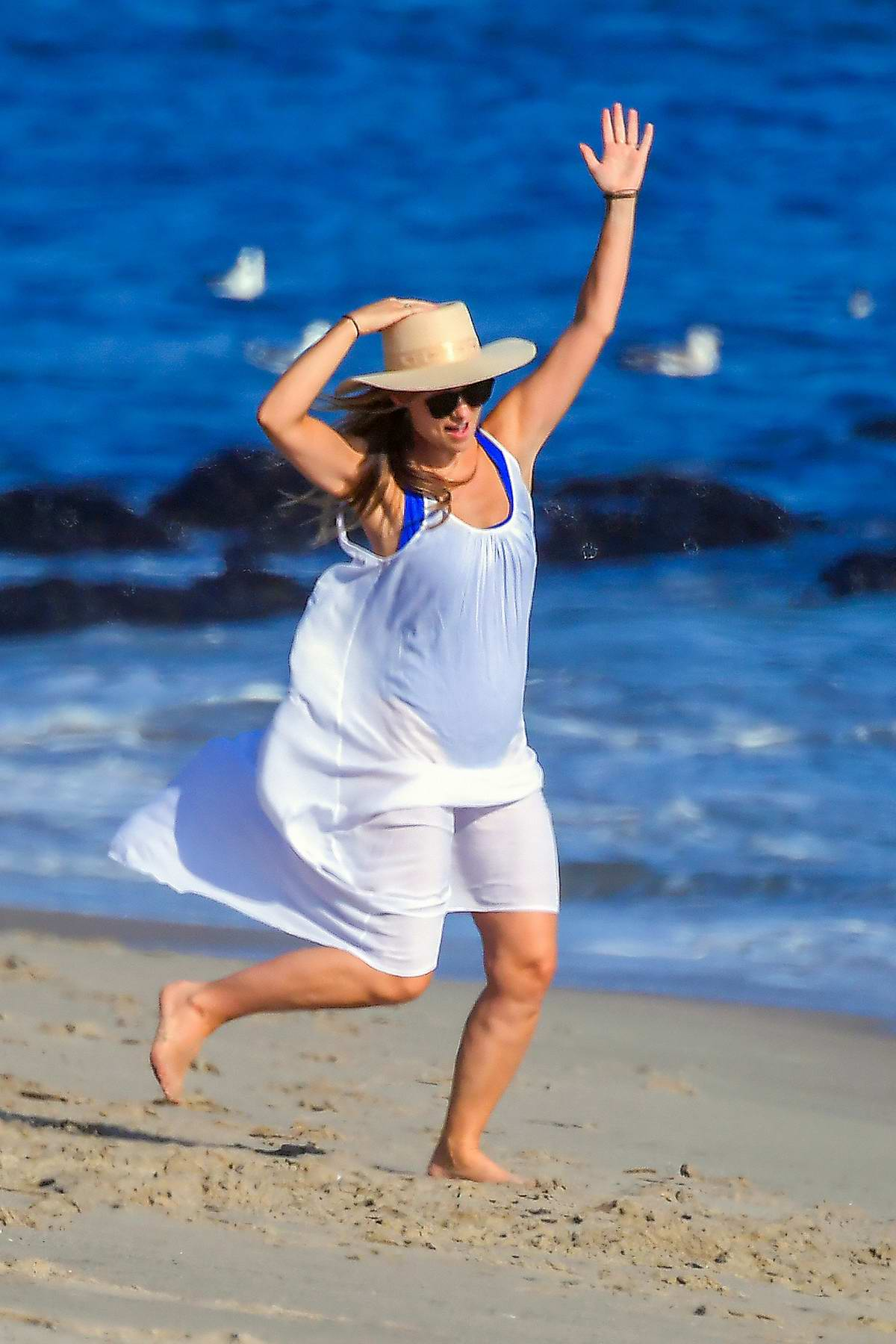 Olivia Wilde seen wearing a white cover-up dress while enjoying a beach day in Santa Monica, California