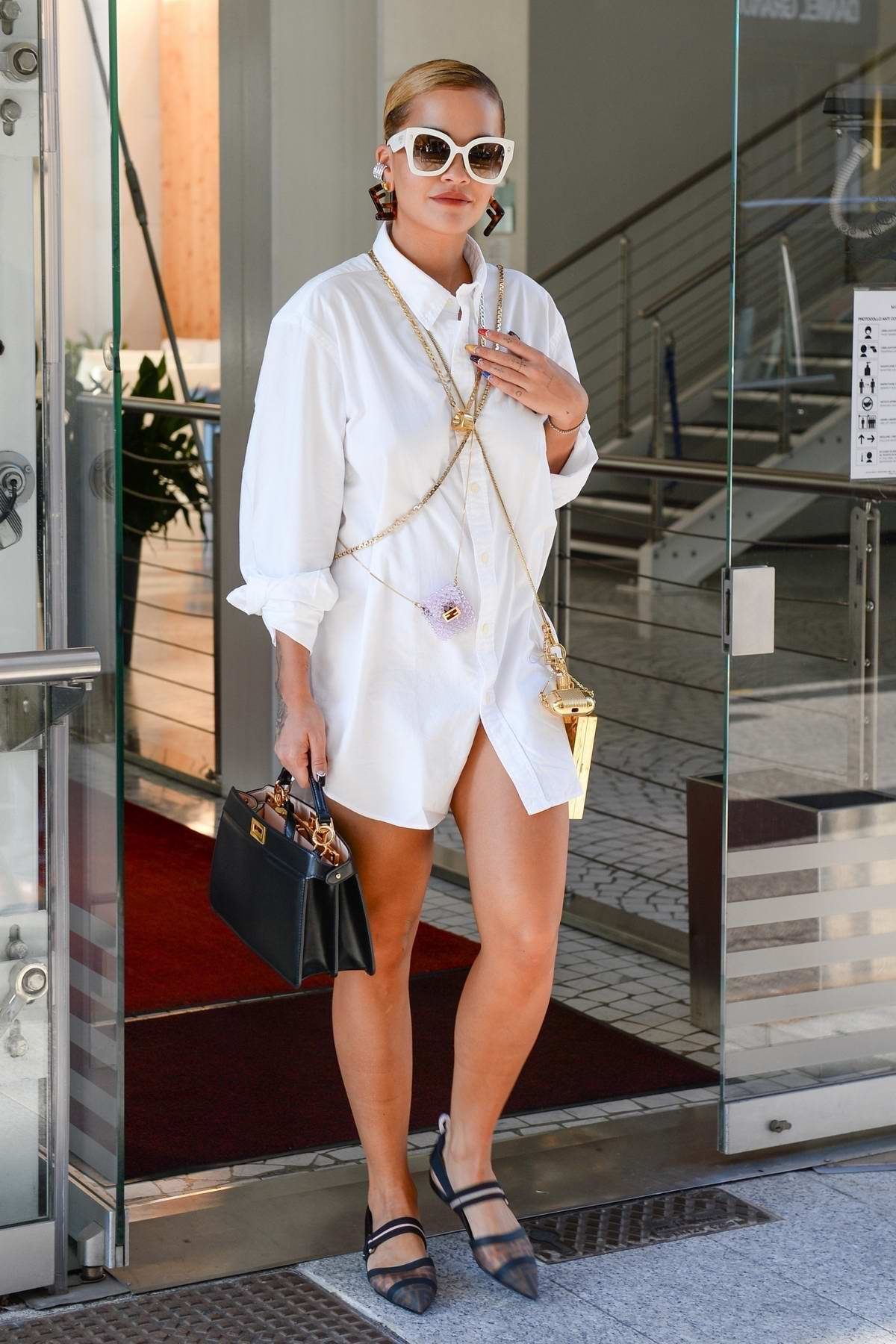 Rita Ora looks chic in white as she leaves her hotel during Milan Fashion Week in Milan, Italy