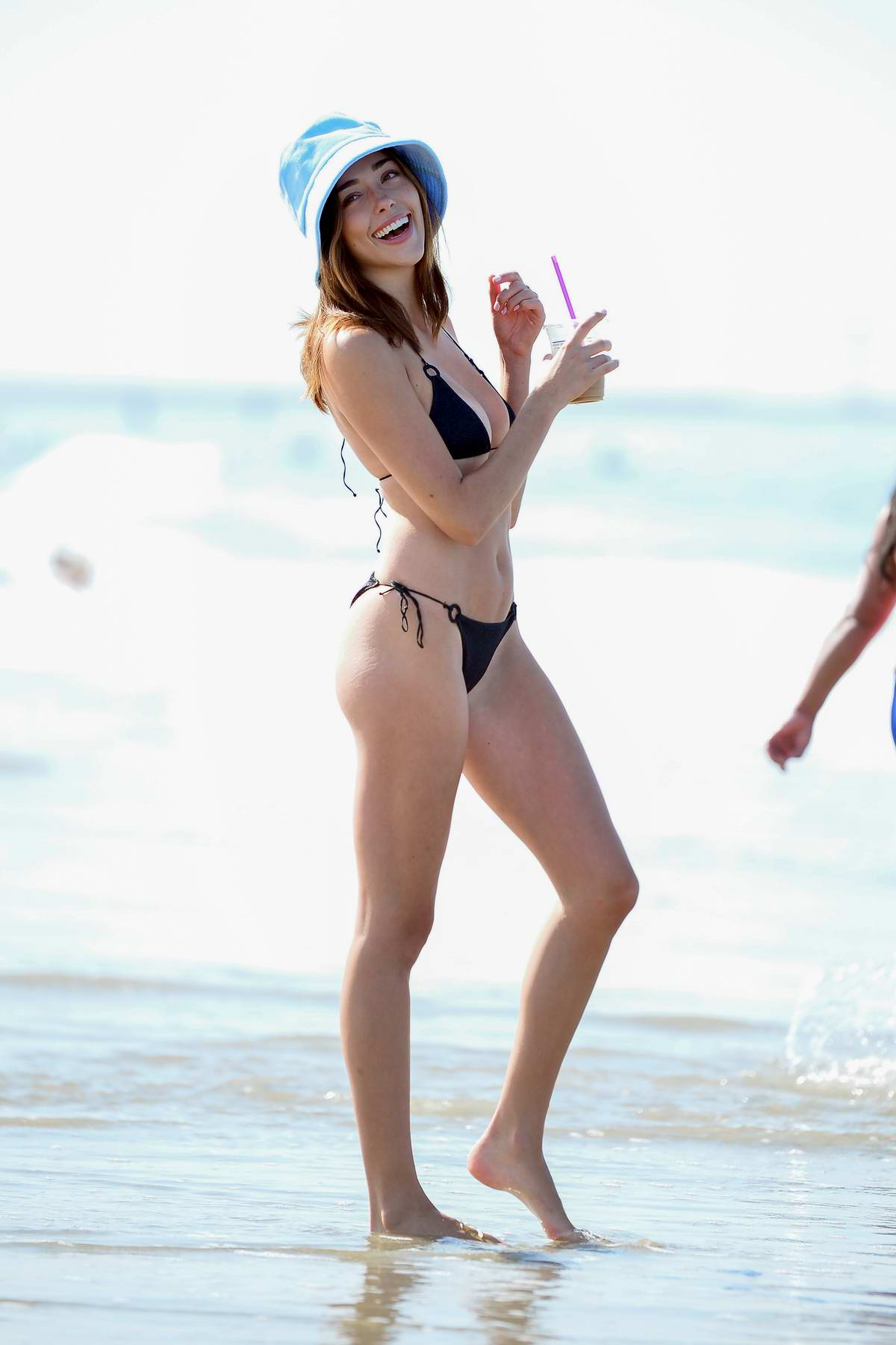 Sophia Culpo sports a black bikini and a bucket hat during a beach day with friends in Venice, California