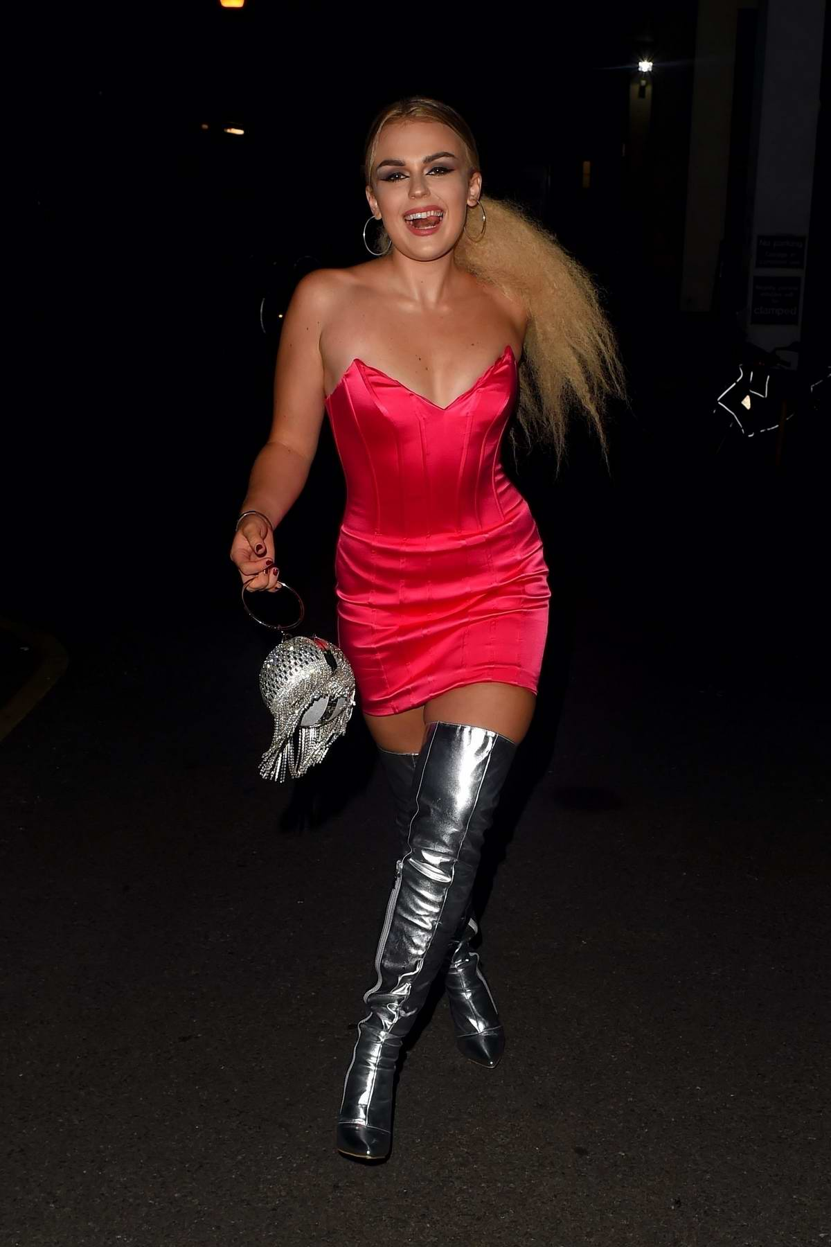 Tallia Storm dazzles in a pink minidress with a pair of thigh-high silver boots during a night out in London, UK