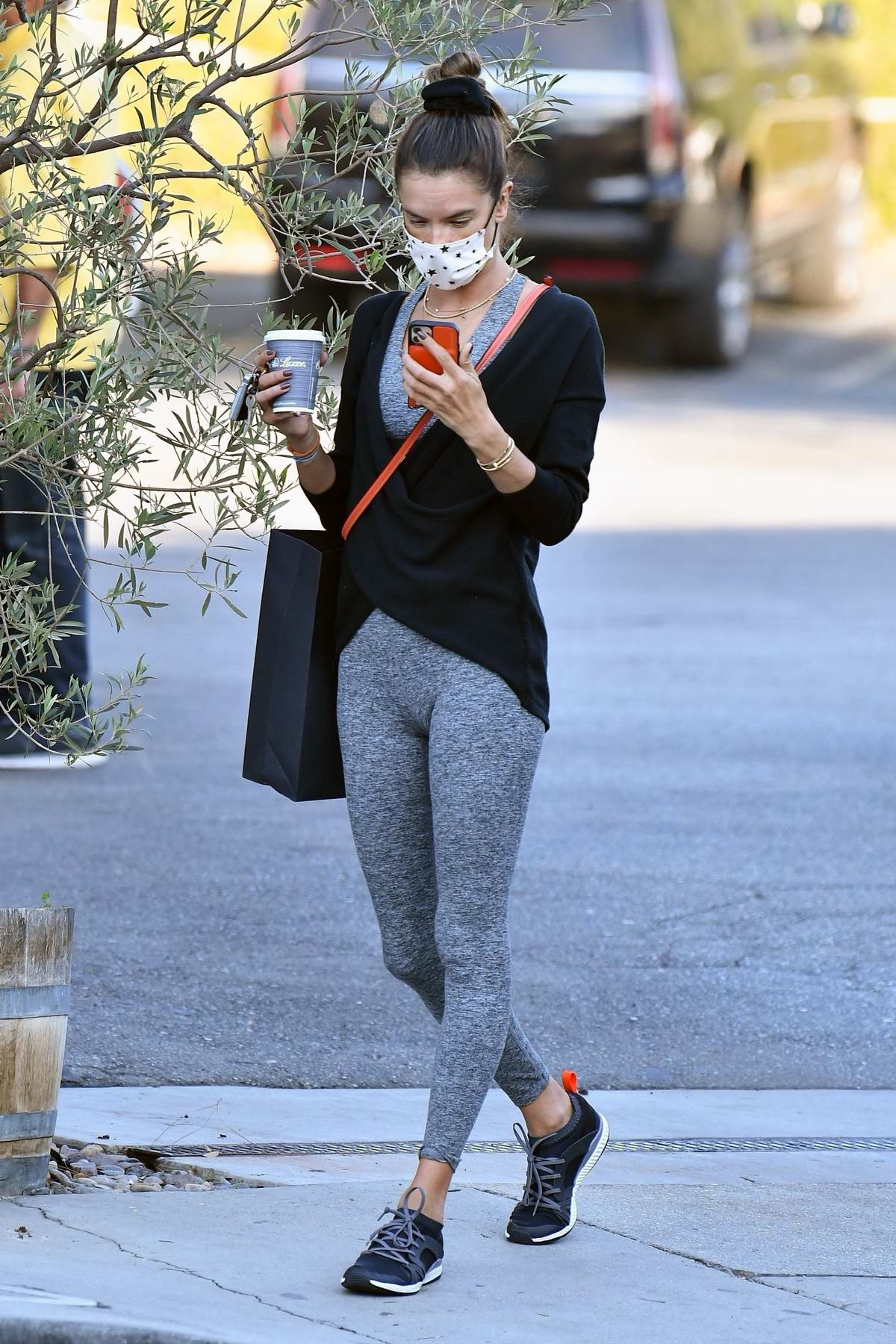 Alessandra Ambrosio chats on her phone while she takes her kids out for ice cream in Brentwood, California