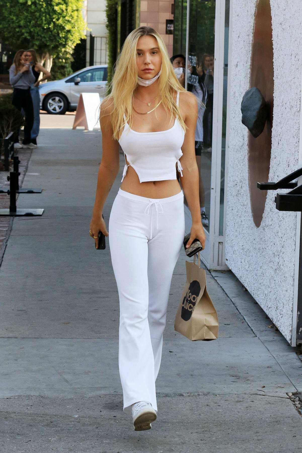 Alexis Ren flaunts her curves in white crop top and tight-fitting pants during a juice run at Moon Juice in Los Angeles