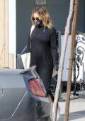 Ashley Tisdale shows her baby bump in a black maxi dress while shopping in West Hollywood, California