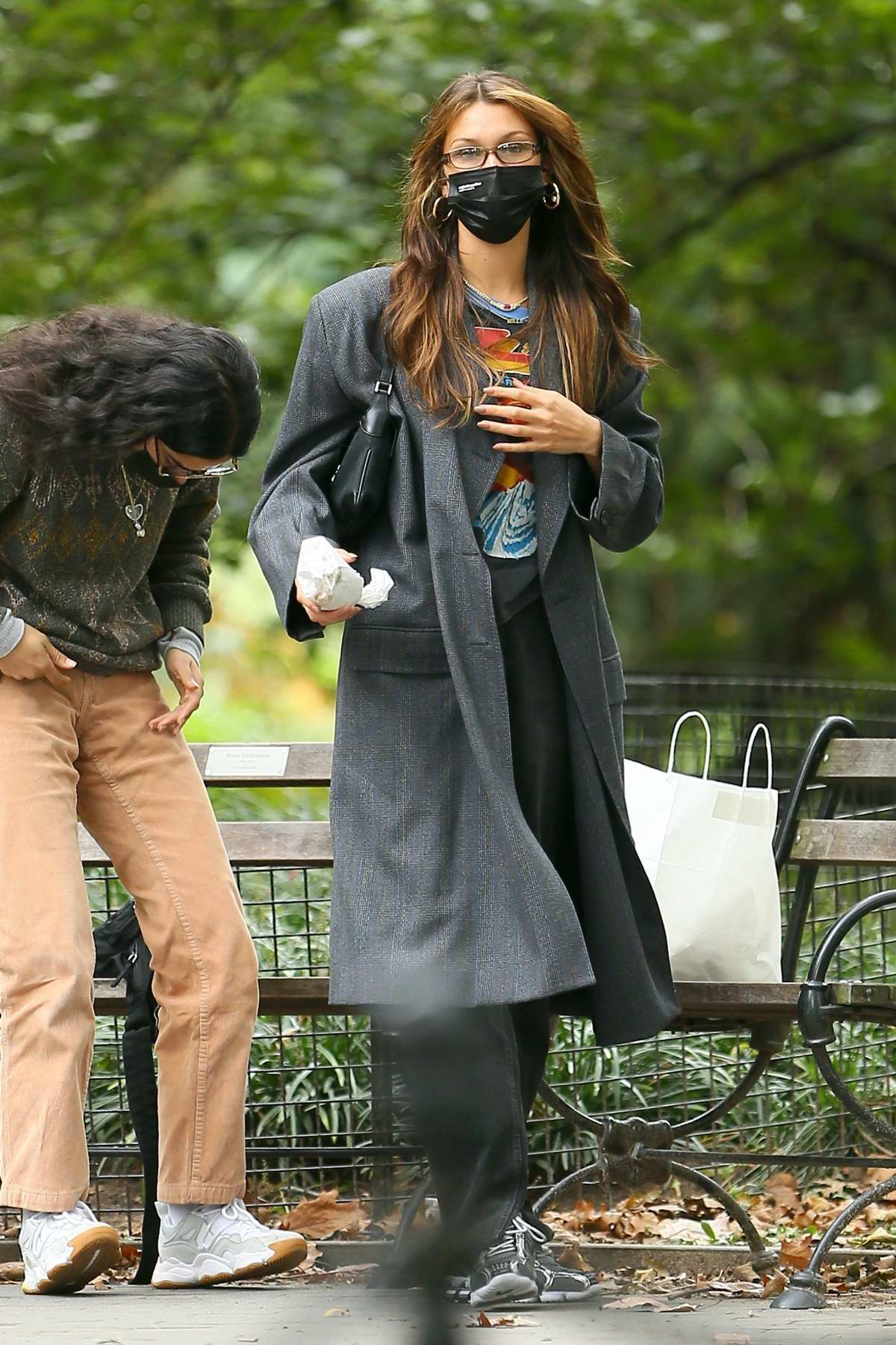 Bella Hadid enjoys lunch with a friend on a park bench in Washington Square Park in New York City