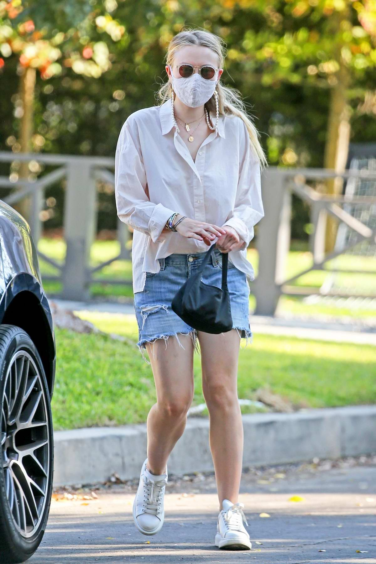 Dakota Fanning wears a white shirt and denim cut-offs while picking up some boxes at a UPS Store in Studio City, California