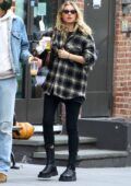 Elsa Hosk covers her baby bump with an oversized flannel shirt during a coffee run in Soho, New York