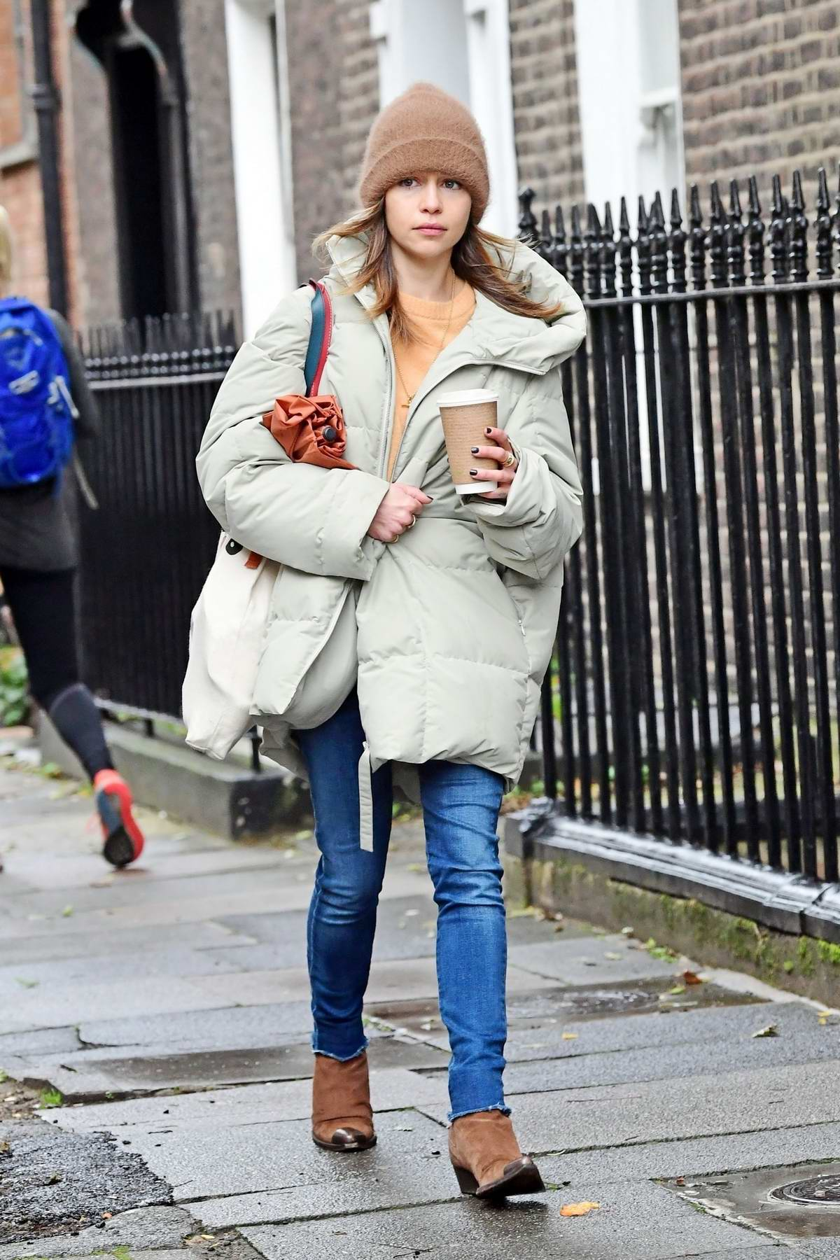 Emilia Clarke bundles up in an oversized puffer jacket and a beanie while running errands in London, UK
