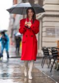 Emily Ratajkowski looks vibrant in a bright red trench coat as she steps out for lunch on a rainy day in New York City