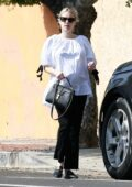 Emma Roberts pairs a white top with black trousers while visiting a friend in Los Angeles