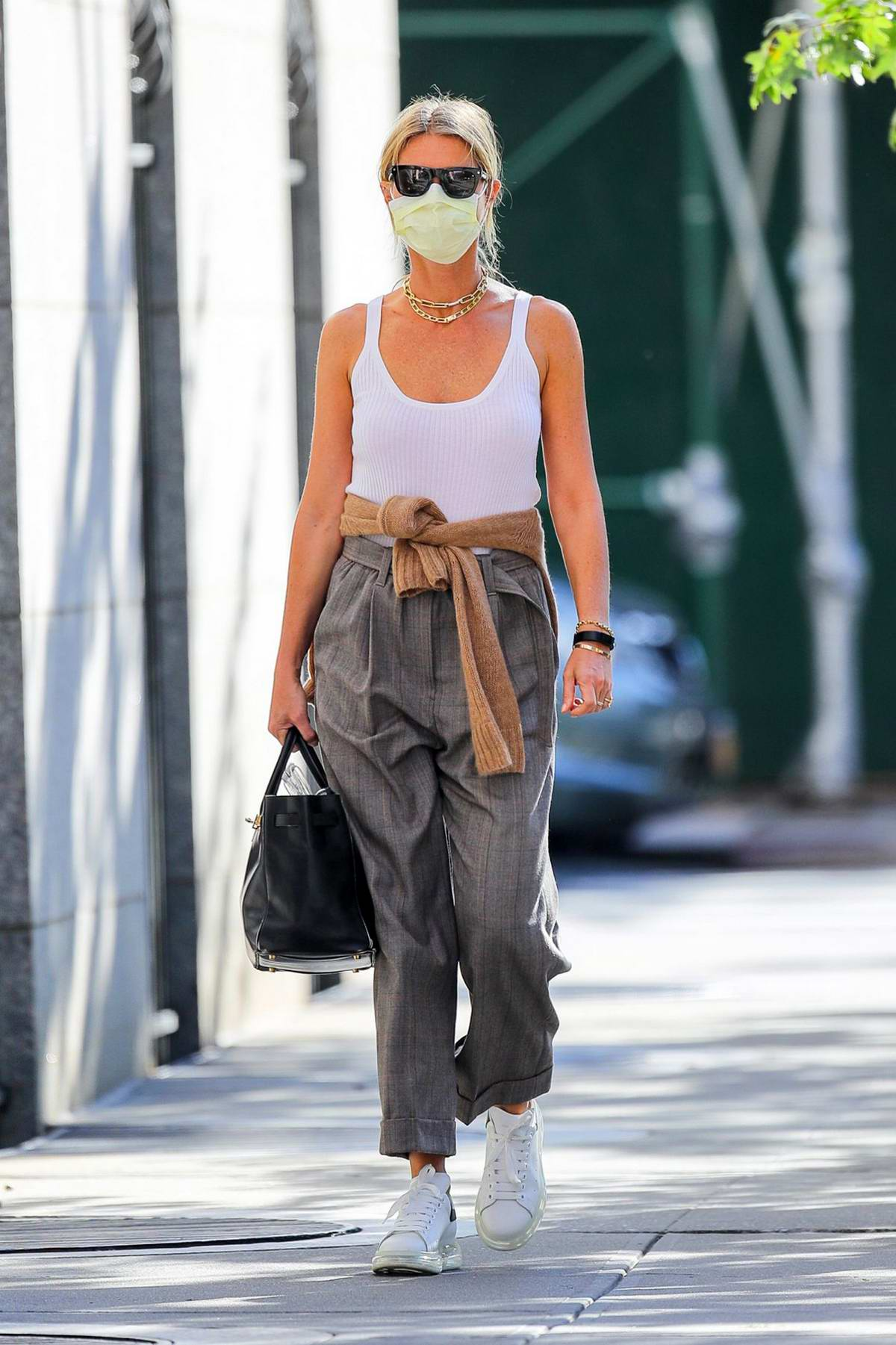 Gwyneth Paltrow keeps it stylish in a white tank top and gray trousers as she steps out in New York City