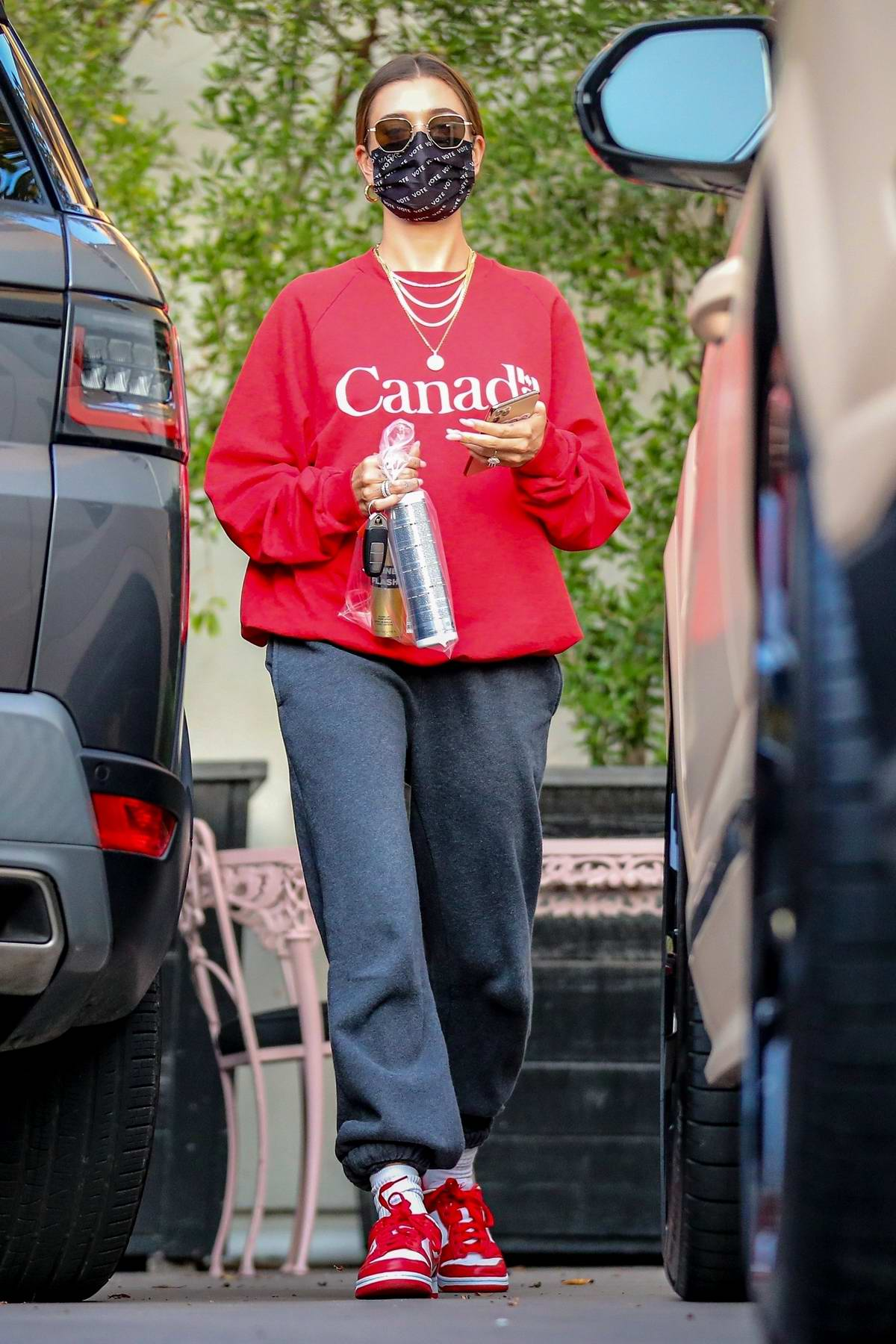 Hailey Bieber wears a red sweatshirt and gray sweatpants for salon visit in West Hollywood, California