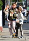 Hilary Duff wears a green bomber jacket and tie-dye joggers while out for an iced coffee with her kids in New York City