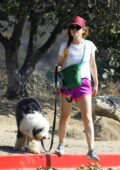 Isla fisher stands out in bright pink shorts as she takes her dog for a hike in Los Angeles
