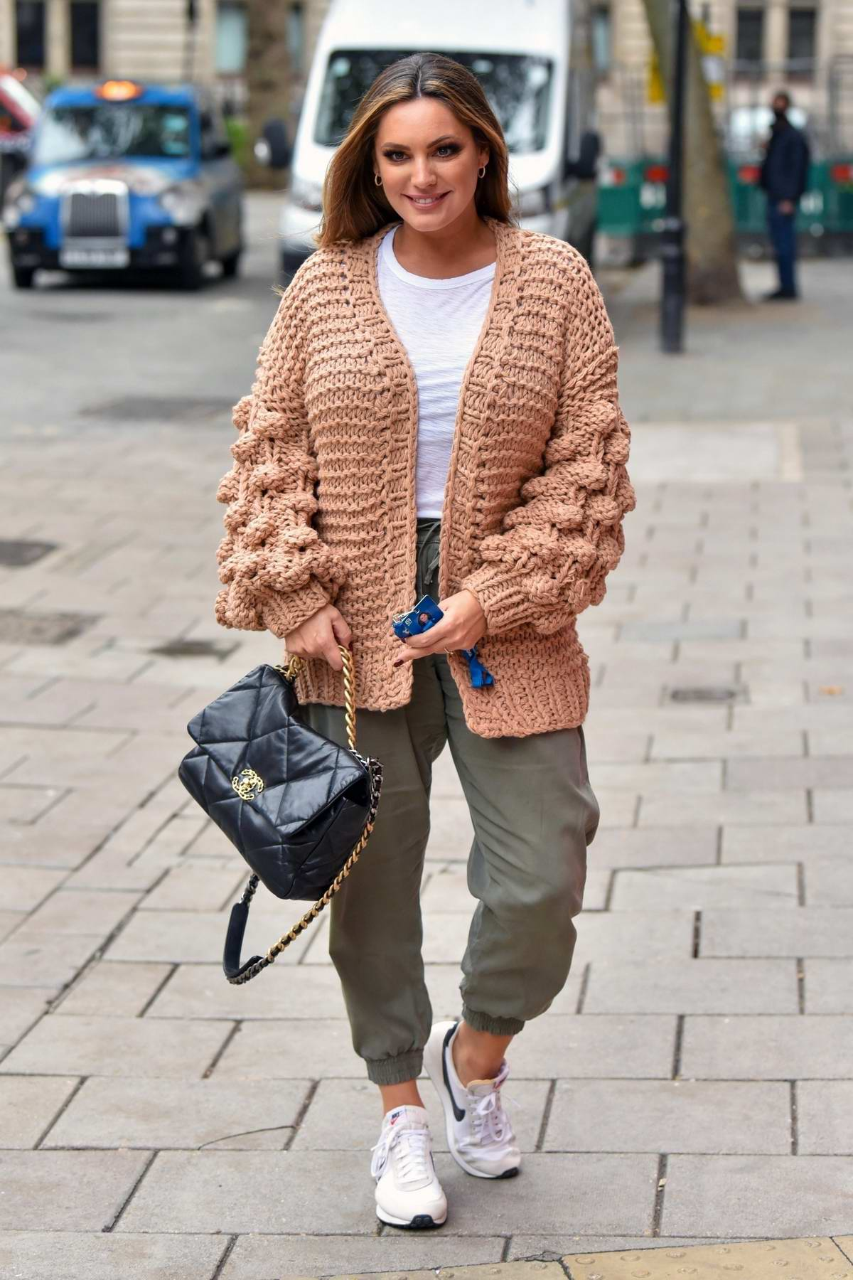 Kelly Brook looks cozy in a knitted cardigan as she arrives for her Heart radio show in London, UK