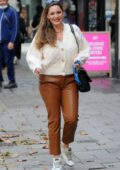 Kelly Brook seen wearing tan leather pants and Golden Goose sneakers as she arrives at Heart Radio in London, UK