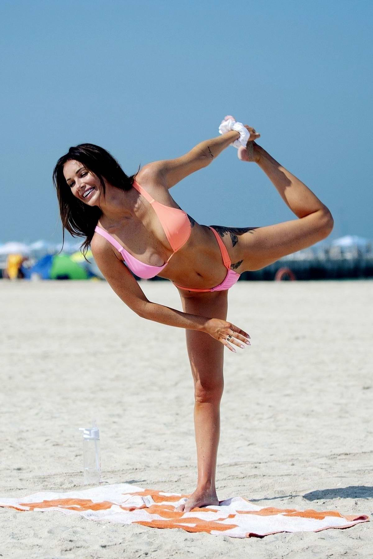 Laura Anderson wears a two-toned pink and orange bikini during a beach yoga session in Dubai, UAE