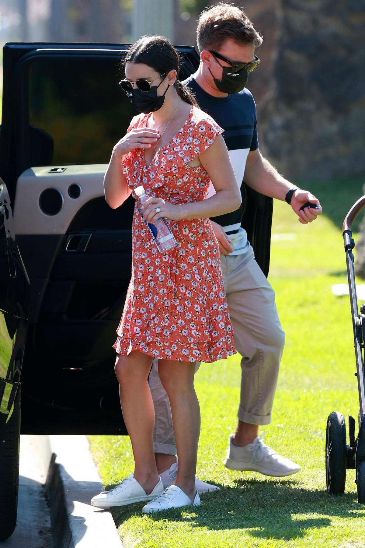 Lea Michele wears an orange floral print dress as she takes her baby out for an afternoon walk in Brentwood, California