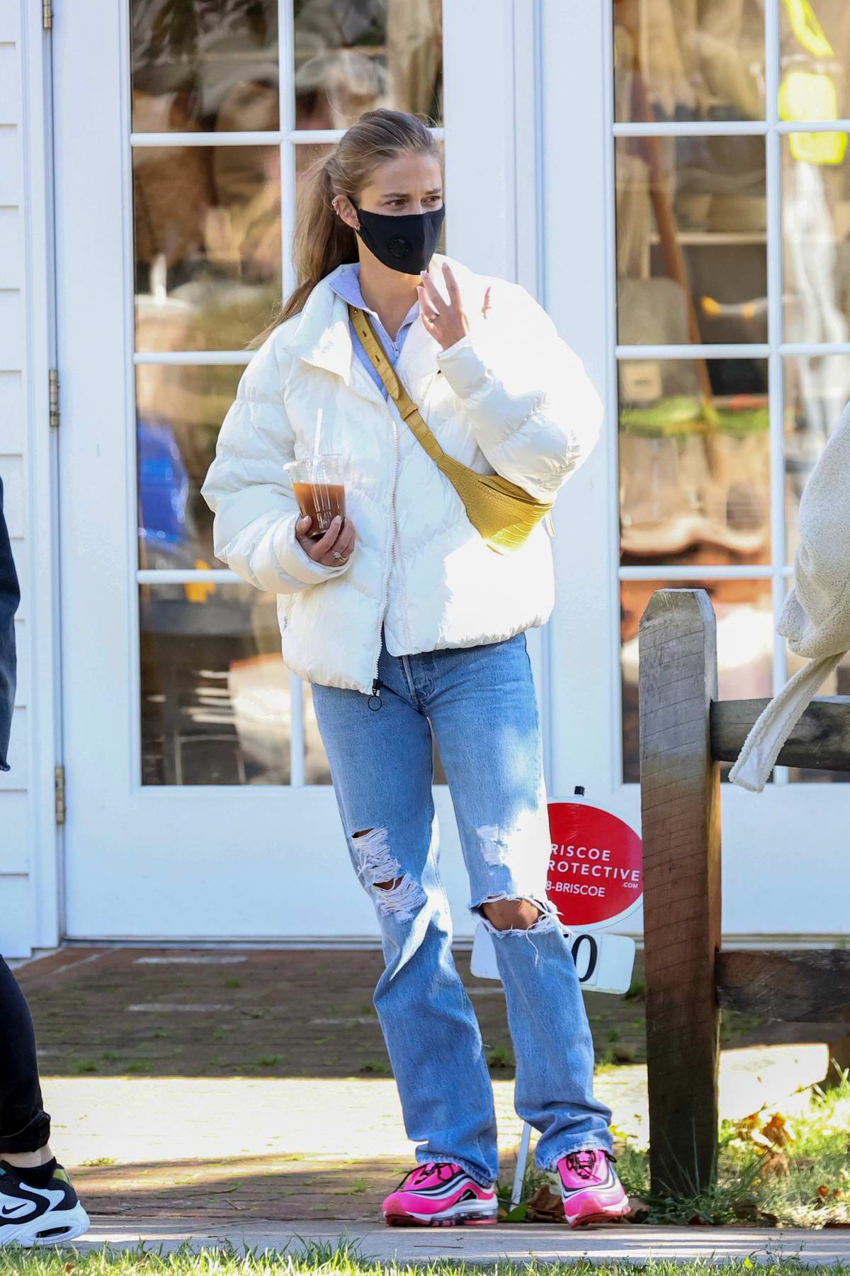 Nina Agdal wears a white puffer jacket with ripped denim and pink Nike sneakers while out for a coffee in New York