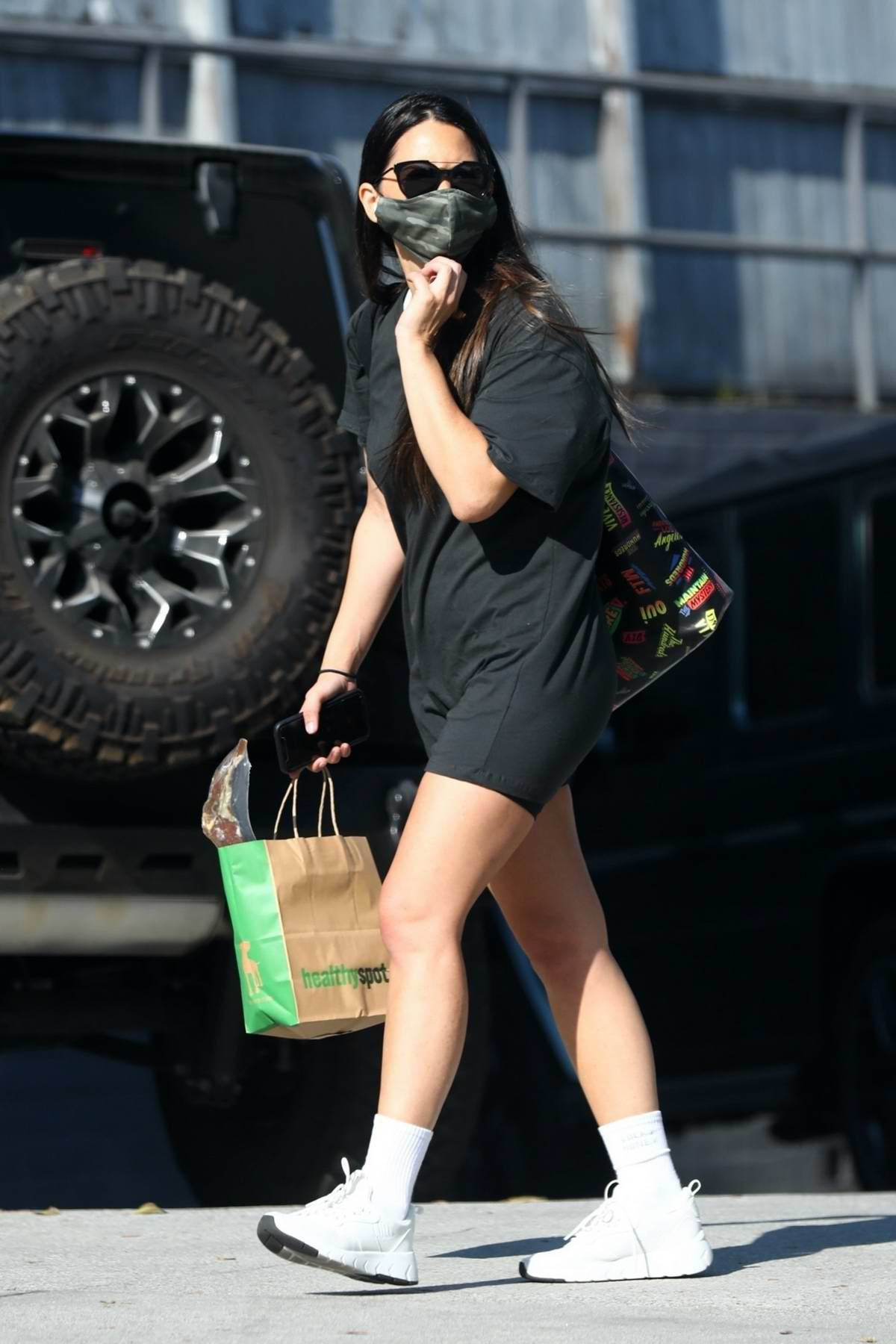 Olivia Munn flaunts her legs in an oversized black t-shirt and shorts while making a stop at Healthy Spot in West Hollywood, California