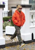Rita Ora rocks bright orange puffer jacket with camo pants as she leaves her home in London, UK