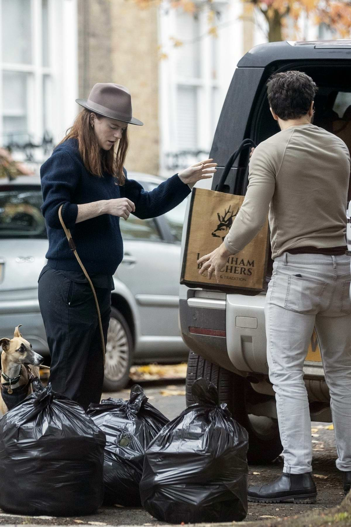 Rose Leslie shows her baby bump while Kit Harrington loads some luggage into the car in London, UK
