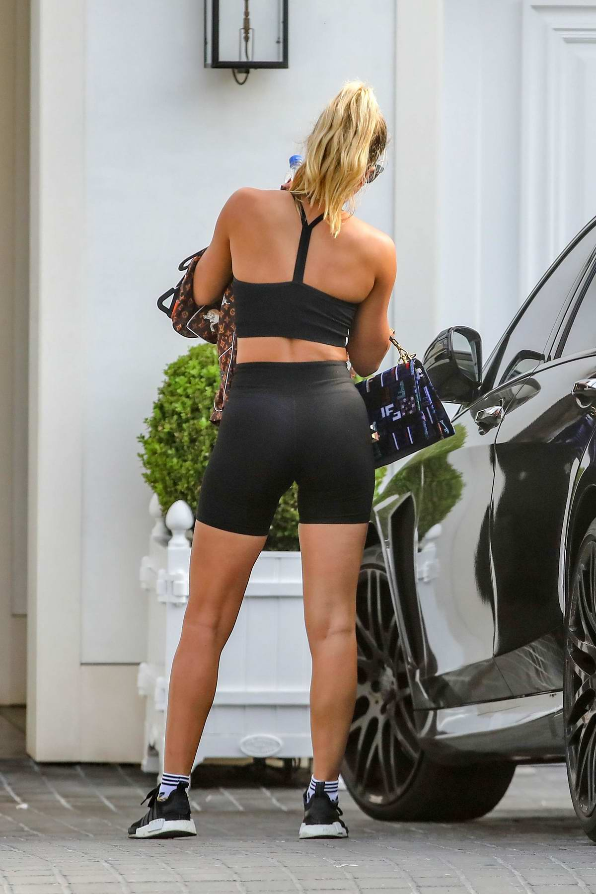 Sofia Richie displays her toned body in black sports bra and legging shorts as she heads out in Malibu, California