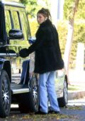 Bella Hadid bundles up in a black coat while visiting a friend in Beverly Hills, California