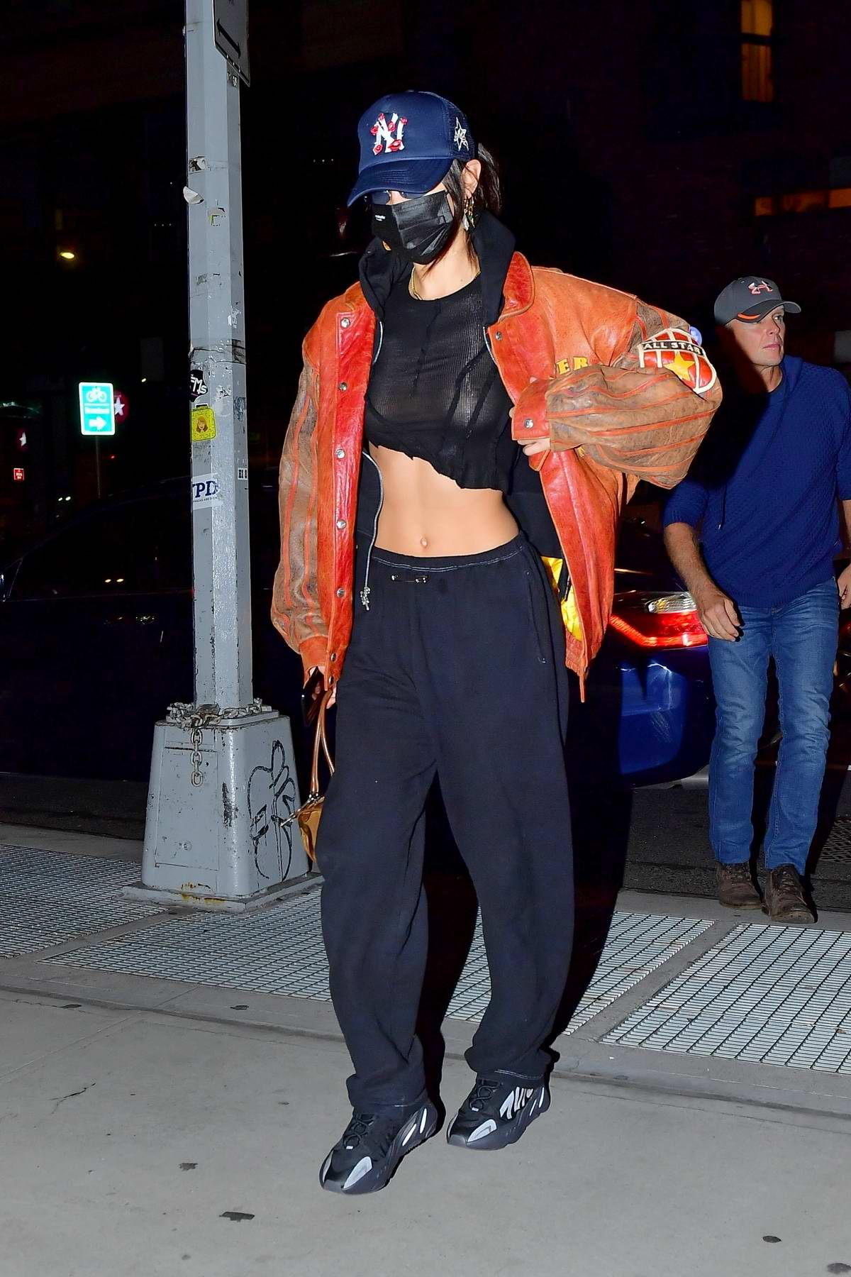 Bella Hadid flaunts her taut midriff in a semi-sheer black crop top as she steps out in Manhattan, New York