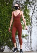 Candice Swanepoel displays her fit physique in a rust-colored bodysuit while out for a run with a friend in Miami, Florida